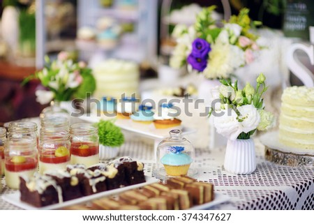 Decorated colorful cupcakes and desserts on a sweet table on some festive event