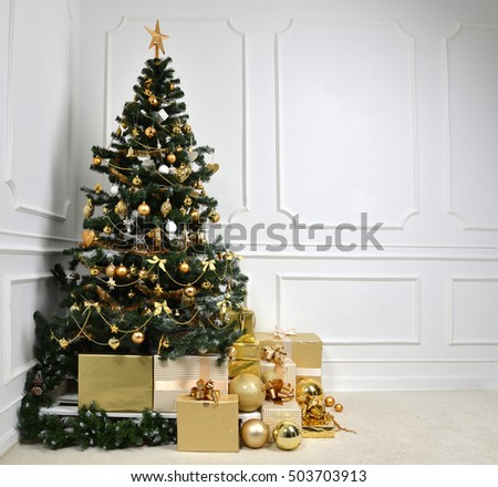 Decorated gold Christmas tree with golder patchwork ornament artificial star hearts presents for new year on white background