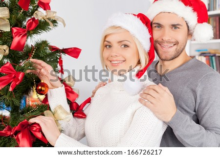 Decorating a Christmas tree together. Cheerful young couple decorating a Christmas tree together