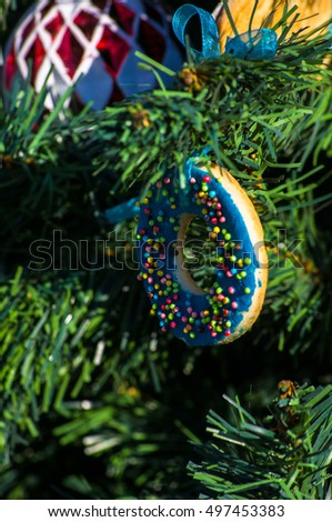 Decoration of Christmas tree with balls, gingerbreaad and ribbons