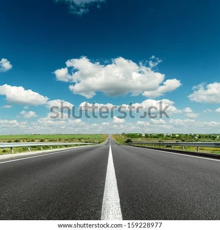 deep blue cloudy sky over asphalt road