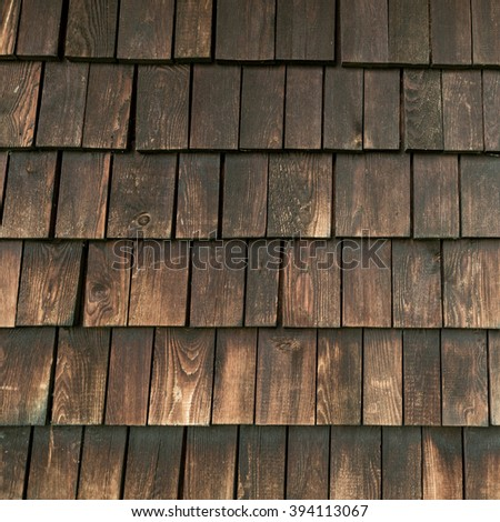 Deep brown traditional wooden roof tiles surface texture as background image on austrian alpine hütte