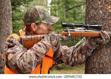 deer hunter aiming rifle in woods
