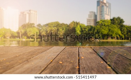 Defocus blur terrace wood and water, trees and building inside. Park view in city, natural background. Lumpini park, Bangkok Thailand.
