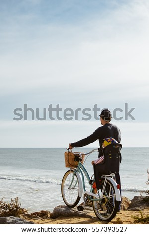 Defocused silhouette of child and father with bike on a beach natural outdoor. Travel vacation background