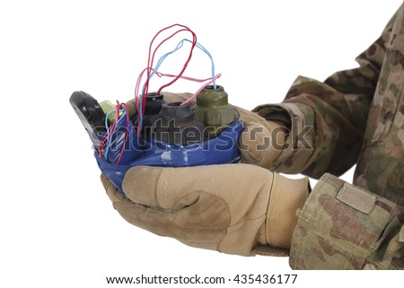 defused improvised explosive device (IED) in hand