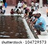 DELHI, INDIA - AUGUST 14: Unidentified Indian people make ablution in front of Jama Masjid, India's largest mosque on  August 14, 2011 in Delhi, India - stock photo