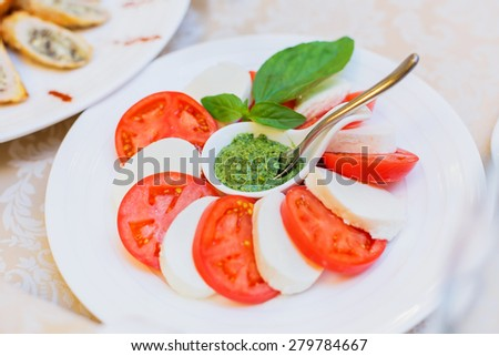 Delicious appetizer close-up. Fresh tomatoes and cheese with spicy hot sauce. Holiday banquet menu