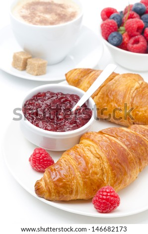 delicious breakfast - fresh croissant with raspberry jam, berries and cup of coffee on white