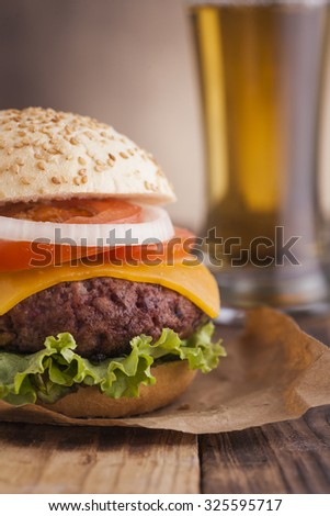 Delicious burger with beef, tomato, cheese and lettuce with a beer glass