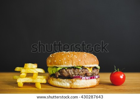 Delicious burger with meat, cheese, lettuce and french fries on a dark background