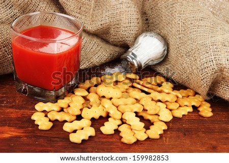 Delicious crackers with salt and tomato juice on wooden table on sackcloth background