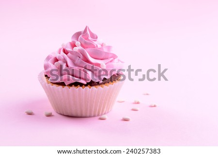 Delicious cupcake on pink background