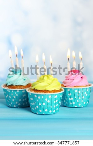 Delicious cupcakes with candles on blue wooden table against blurred background