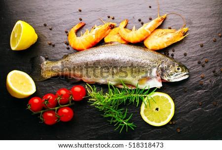 Fresh fish dorado vegetables on dark stock photo 389898724 for Aromatic herb for fish