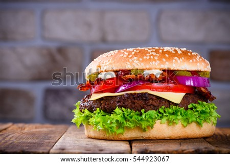 Delicious fresh hamburger on wooden table. Big burger in classic american style with hot grilled patty with melted cheese on top, tomato, onion and sauces.