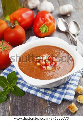 Delicious gazpacho on wooden table and fresh vegetables