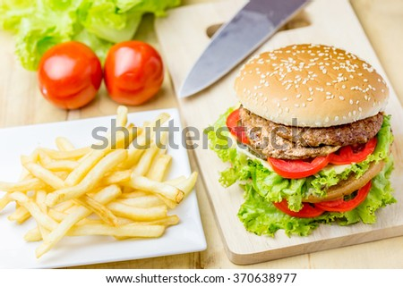 Delicious hamburger and french fries on wooden table