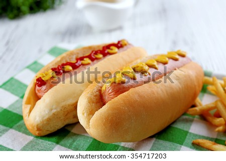 Delicious hot-dogs with French fries on green checkered cotton napkin, close up
