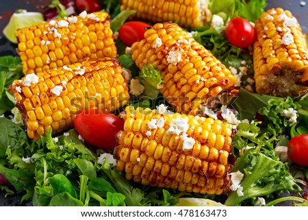 Delicious oven cooked Corn with feta cheese, paprika, lime, vegetables.