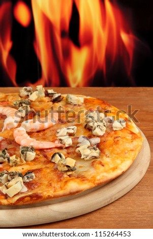 Delicious pizza with seafood on stand on flame background