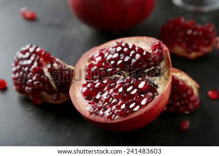 Delicious pomegranate fruit on black background