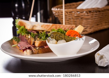 Delicious thinly sliced beef pastrami club sandwich with fresh curly lettuce served with a small dish of pickled vegetables on a white plate, isolated on white