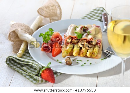 Delicious toast with fried white asparagus, Spanish serrano ham, mushrooms  and melted cheese, served with some strawberries and a glass of white wine