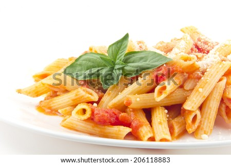 Delicious vodka penne garnished with basil leaves and isolated on white