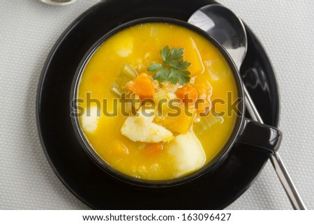Delicious warming hearty vegetable soup with a parsley garnish.