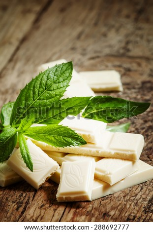Delicious white chocolate with mint on an old wooden table, selective focus