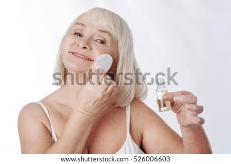 Delighted elderly woman having her daily skin care routine