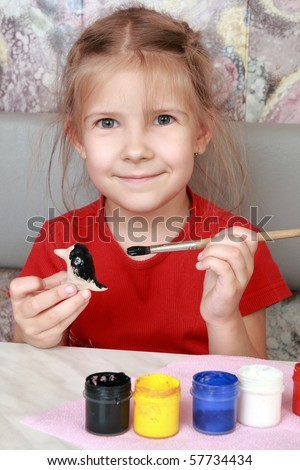 Delighted little girl paints a clay figurine