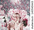 Delighted loving woman celebrating a wedding amongst falling flower confetti. Romantic celebration - stock photo