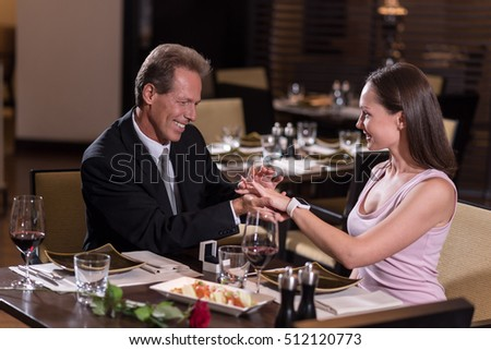 Delighted young woman getting a proposal from an aged man