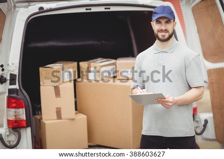 Delivery man writing on clipboard in front of his van