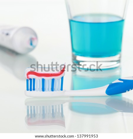 Dental hygiene with a toothpaste on a toothbrush and rinse