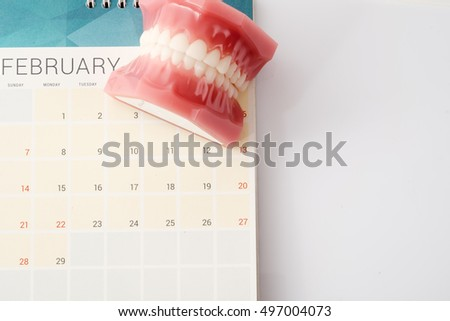 Dentist demonstration teeth model with flesh pink gums on calendar; concept for dental appointment