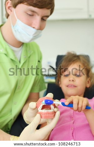 Dentist shows to patient girl how to correctly brush teeth. For clarity, doctor uses an artificial jaw. Focus on jaw.