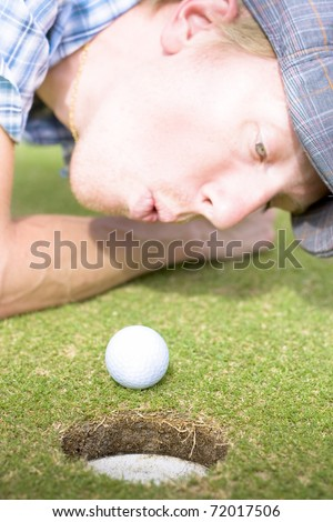 Desperately Wanting A Hole In One Off A Four Par A Golfer Puffs On A Golf Ball To Motion It Into The Hole In A Funny Golfing Cheat Concept
