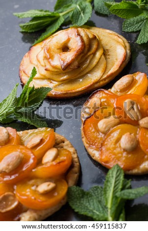 Dessert with apricot and apple. Traditional french pie tart with fruits on dark marble background. Decorated almonds and mint leafs. Delicious dessert with copy space closeup.