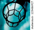 Detail of a basketball basket against the cloudy sky. - stock photo