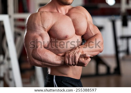 detail of a bodybuilder posing in the gym: side chest