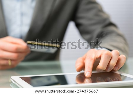 Detail of a business person shopping online - entering a credit card number on a tablet computer.