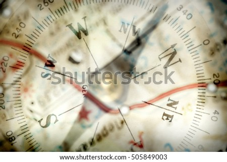 Detail of a magnetic compass on the background of the blurred image of the geographical map