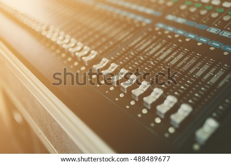 Detail of a music mixer in studio, dj working for new tracks. Music production with editing tools.Flare effect.Selective focus.