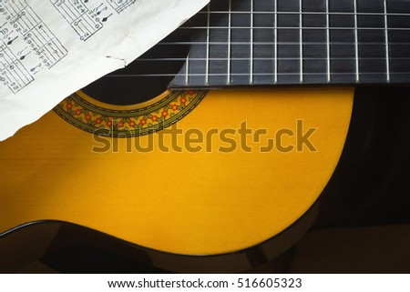 Detail of acoustic guitar on a score background. Selective focus