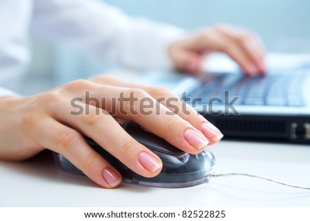 Detail of female hands using a computer on office background