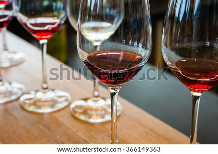 Detail of glasses with red wine samples, on wood counter.