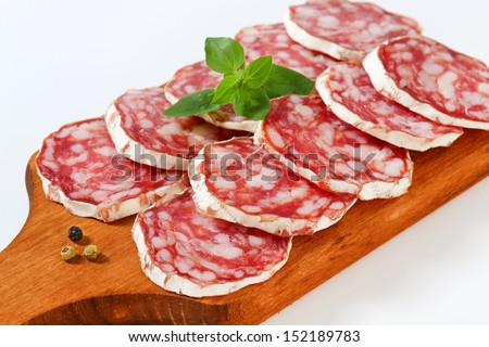 detail of wooden cutting board with sliced salami
